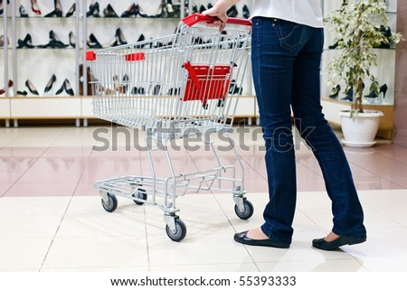 Lower half waist down image of woman in jeans pushing a shopping cart in a shoe store