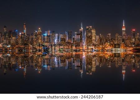 Lower Manhattan skyline at night reflected in water #244206187
