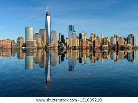 Lower Manhattan skyline panorama over East River with reflection and blue sky in New York City #131039210