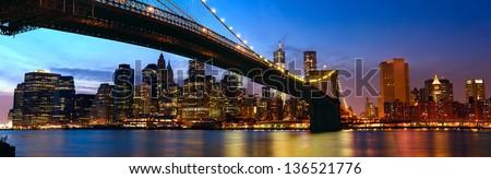 Lower Manhattan skyline panorama with Brooklyn Bridge at sunset in New York City #136521776