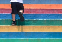 Lower part of a boy in casual shoe walking up outdoor colorful stair,children lifestyle successful concept