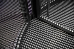 Lower part of revolving doors and striped floor under them. Abstract modern architecture. Steel and glass. Close-up photo of office building lobby / entrance hall fragment.