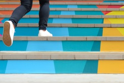 Lower part of teenage girl in casual shoe walking up outdoor colorful stair,teenage lifestyle successful concept