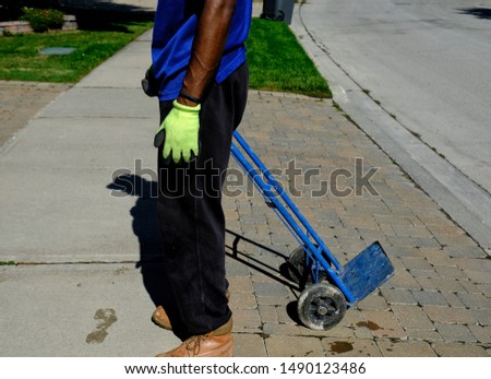 Lower part of worker seen on street holding empty blue dolly or trolly