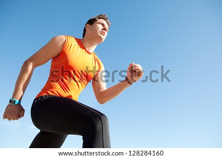 Lower perspective view of a professional olympic sports man running against a bright blue clean sky.