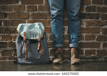 Lower section of man in denim trousers and sneakers standing with backpack near brick wall