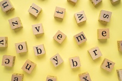 Lowercase alphabets on a wooden cube with a yellow background.