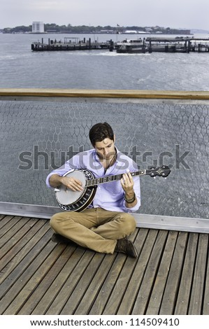 Lowering his head  and sitting on the deck a young musician is playing a banjo
