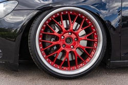 Lowrider custom tuned sport car wheel with small rubber tyre and large disk, close up