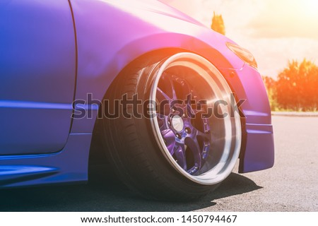 Lowrider custom tuned sport car wheel with small rubber tyre and large disk, close up #1450794467