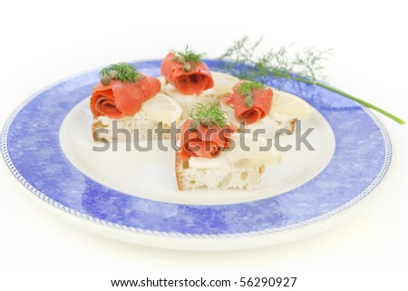 Lox hors d'ouvre, smoked salmon appetizers, on a plate with blue rim