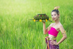 Loy Krathong Festival;woman in thai traditional outfit holding decorated buoyant