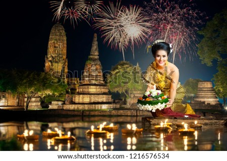Loy krathong thailand festival. Asia thai woman wearing Traditional  dress are culture costume floating Krathong in the river at evening time Thailand with temple light up and fireworks.