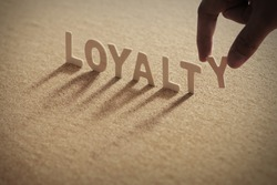 LOYALTY wood word on compressed board with human's finger at Y letter
