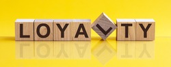 LOYALTY - wooden blocks with letters, front view on yellow background, the image is mirrored in the glossy surface, business concept background