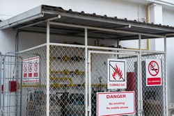 LPG supply system zone that is dangerous area and contain gas tank has caution sign such as flammable gas, no smoking and no mobile phone. gas transportation equipment for industry in steel warehouse.