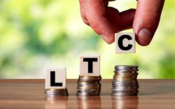 LTC word symbol - business concept. Hands put wooden block on stacked increasing coin.