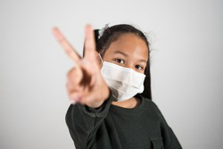 Lttle girl with medical mask show v sign with hand, healthcare and infection control. Concept of positivism against the infection of the coronavirus, quarantine kids.