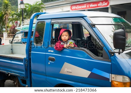 LUANG PRABANG, LAOS - DEC 8: Unidentified cute boy looks out the window of his father cargo car at asian city street on Dec 8, 2013 in Luang Prabang, Laos