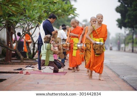 LUANG PRABANG, LAOS- JULY 7, 2011 : Monks gathering morning alms in Luang Prabang.The tradition of giving alms to monks in Luang Prabang has been extended to tourists.