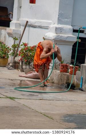 Luang Prabang, Laos - March 23, 2019 :  Monk washing with garden hose outside temple in Luang Prabang, Laos. #1380924176