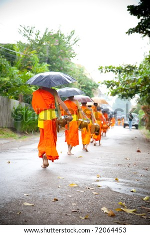 LUANG PRABANG, LAOS - OCTOBER 16 : Buddhist novices walk to collect alms and offerings on Oct 14, 2010 in Luang Prabang, Laos. This procession is held every day.