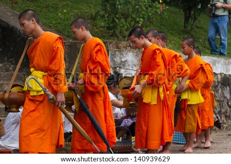 LUANG PRABANG, LAOS - SEPTEMBER15; Unidentified monks walk to collect alms and offerings on September 15, 2012 Laos. This procession is held every day in Luang prabang in the early morning