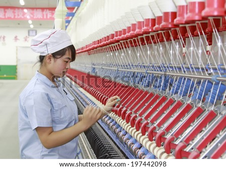 LUANNAN, CHINA - MAY 4: Women were spinning production line operation in production workshop, on May 4, 2014, Luannan county, hebei province, China.