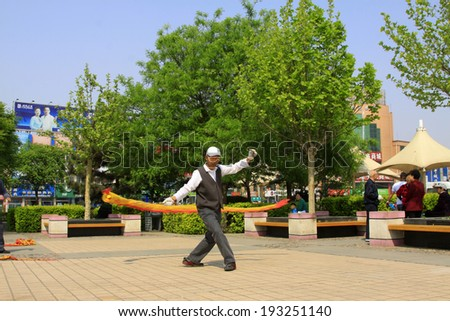 LUANNAN COUNTY, CHINA - APRIL 29: An old man was shaking diabolo on the Square, on april 29, 2014, Luannan county, Hebei province, China