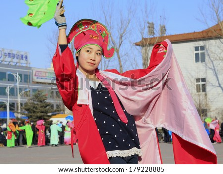LUANNAN COUNTY, CHINA - FEBRUARY 9: Girl wearing colorful clothes, performing yangko dance in the street, during the Chinese Lunar New Year, February 9, 2014, Luannan County, Hebei Province, China.