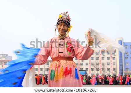 LUANNAN COUNTY - FEBRUARY 15: Old man wearing colorful clothes, performing yangko dance in the street, during the Chinese Lunar New Year, February 15, 2014, Luannan County, Hebei Province, China.