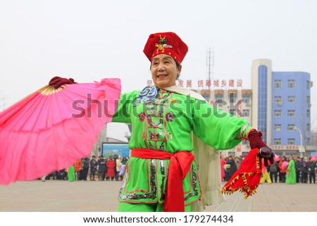LUANNAN COUNTY - FEBRUARY 15: Old woman wearing colorful clothes, performing yangko dance in the street, during the Chinese Lunar New Year, February 15, 2014, Luannan County, Hebei Province, China.