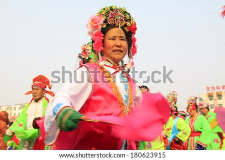 LUANNAN COUNTY - FEBRUARY 13: People wearing colorful clothes, performing yangko dance in the street, during the Chinese Lunar New Year, February 13, 2014, Luannan County, Hebei Province, China.