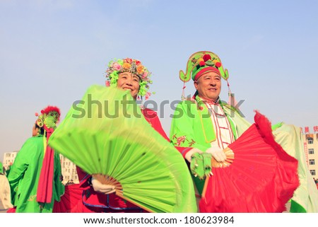 LUANNAN COUNTY - FEBRUARY 11: People wearing colorful clothes, performing yangko dance in the street, during the Chinese Lunar New Year, February 11, 2014, Luannan County, Hebei Province, China.