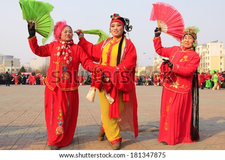 LUANNAN COUNTY - FEBRUARY 12: People wearing colorful clothes, performing yangko dance in the street, during the Chinese Lunar New Year, February 12, 2014, Luannan County, Hebei Province, China.