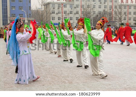 LUANNAN COUNTY - FEBRUARY 8: People wearing colorful clothes, performing yangko dance in the street, during the Chinese Lunar New Year, February 8, 2014, Luannan County, Hebei Province, China.