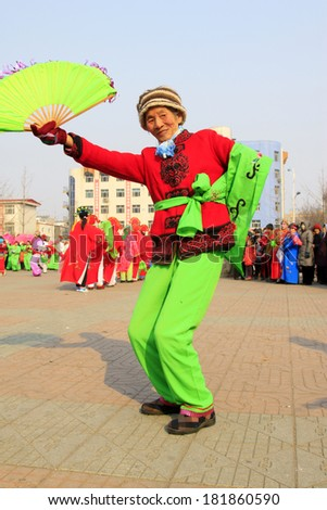 LUANNAN COUNTY - FEBRUARY 12: Woman wearing colorful clothes, performing yangko dance in the street, during the Chinese Lunar New Year, February 12, 2014, Luannan County, Hebei Province, China.