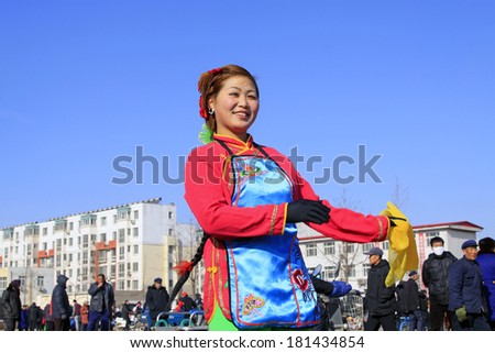 LUANNAN COUNTY - FEBRUARY 10: Young lady wearing colorful clothes, performing yangko dance in the street, during the Chinese Lunar New Year, February 10, 2014, Luannan County, Hebei Province, China.