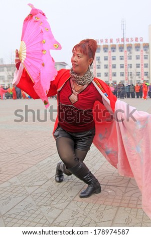 LUANNAN COUNTY - FEBRUARY 15: Young woman wearing colorful clothes, performing yangko dance in the street, during the Chinese Lunar New Year, February 15, 2014, Luannan County, Hebei Province, China.
