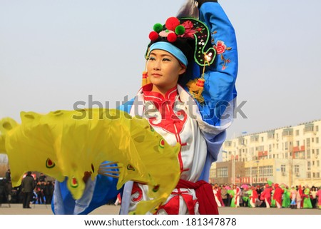 LUANNAN COUNTY - FEBRUARY 12: Young woman wearing colorful clothes, performing yangko dance in the street, during the Chinese Lunar New Year, February 12, 2014, Luannan County, Hebei Province, China.