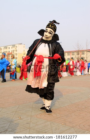 LUANNAN COUNTY - FEBRUARY 13: Zhu bajie\'s image wearing colorful clothes, performing yangko dance in the street, February 13, 2014, Luannan County, Hebei Province, China.
