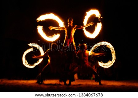 Luau Hawaii, French Polynesia fire dance silhouettes of professional dancers at night on beach resort tiki party.