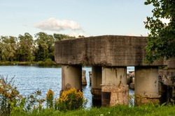 Lucavsala stone bridge pillars ruins in river water during sunny summer day. Scenic photo of pier remains in water framed by green and yellow grass and green trees. Sunny day at Daugavas riverside.
