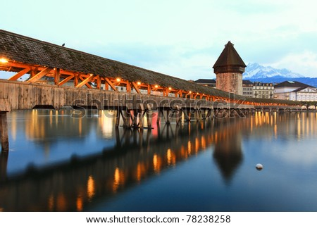 LUCERN, SWITZERLAND - APRIL 14:The Chapel Light show at dusk, closeup on April 14, 2011 in Lucern.The Chapel Bridge is a 204 m (670 ft) long bridge crossing the Reuss River in the city of Lucerne in Switzerland. - stock photo