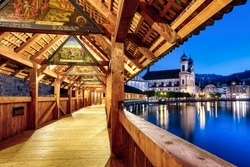 Lucerne city, Switzerland, view of Jesuit church from historical wooden Chapel Bridge, famous for its medieval paintings dating back to the 1630-s years (public domain)