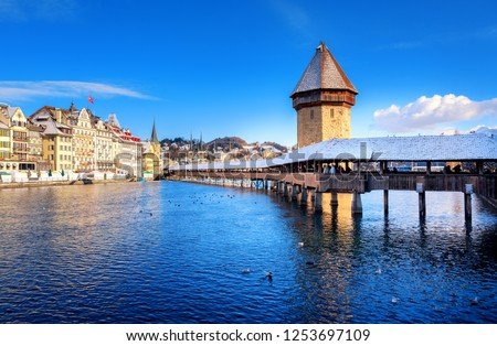 Lucerne, Switzerland, historical Old Town with wooden Chapel Bridge and Water Tower white snow covered in winter