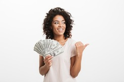 Lucky american woman with curly brown hair holding fan of money dollar banknotes and gesturing finger aside on copyspace isolated over white background