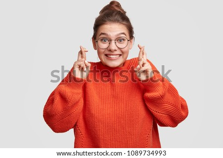 Lucky beautiful Caucasian female crosses fingers , hopes all wishes come true, wears oversized red sweater and spectacles, isolated over white background. People, body language and happiness