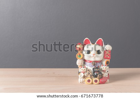 Lucky cat or maneki neko on wooden table background with copy space vintage filter