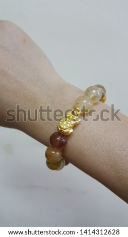 Lucky Charming gemstone beads bracelet on woman hand,  Chinese style amulet for healthy and wealthy with the golden Pixiu or Pi Yao from China